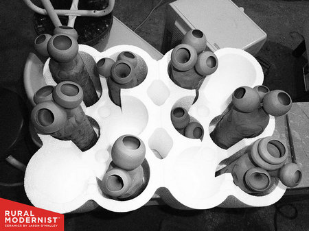 A group of freshly thrown sculptures chill out before heading off to the kiln.